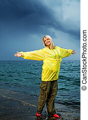 Young woman in yellow raincoat near the ocean at storm