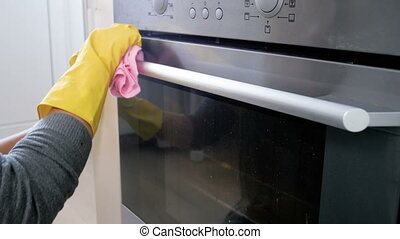 Young woman in yellow rubber gloves cleaning electric oven...