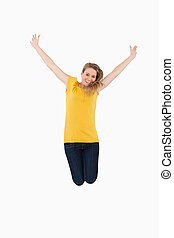 Young woman in yellow shirt jumping while raising arms
