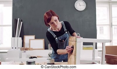 Young woman indoors restoring old furniture. - Young woman ...