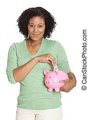 Young woman inserting currency into piggy bank