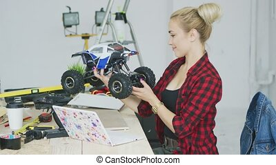 Young woman inspecting radio-controlled car at workbench -...