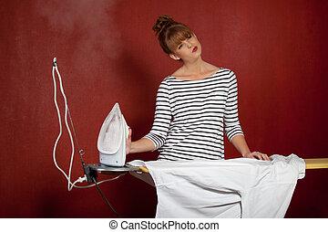 young woman ironing a shirt