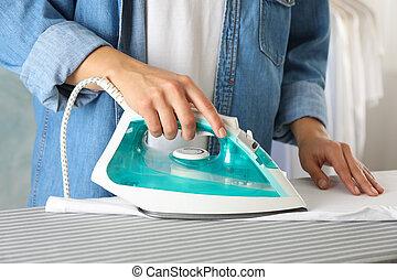 Young woman ironing shirt on ironing board, close up