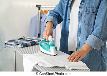 Young woman ironing shirt on ironing board, space for text