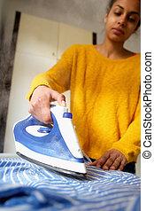 Young woman ironing striped shirt