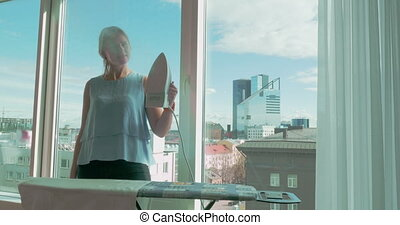 Young woman ironing the clothing by window at home