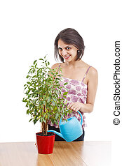 Young woman irrigate plants