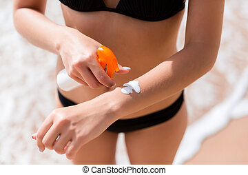 Young woman is applying protective sun cream on her hand at the beach