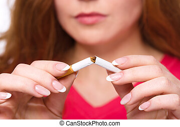 Young woman is breaking a cigarette