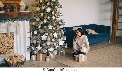 Young woman is bringing gift boxes to Christmas tree and putting them under fir-tree then looking at presents and smiling. New Year and holidays concept.