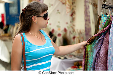 woman is choosing a scarf in a street shop