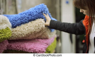 Young woman is choosing carpet at shop