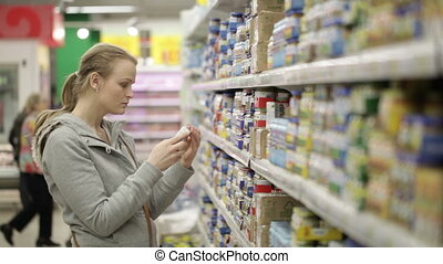 Young woman is choosing food for her child in the shopping center. No visible trademarks or logos. Middle shot with shoppers in background.
