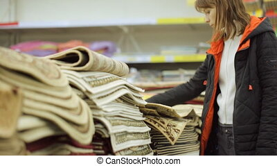 Young woman is choosing rug at shop