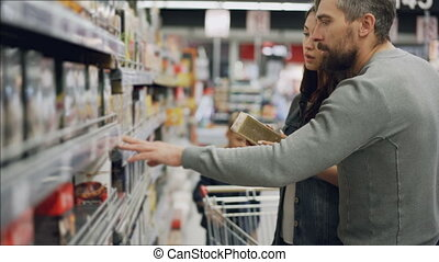 Young woman is choosing tea in food store, her husband and son are helping her looking at products and talking. Buying food and drinks in supermarket concept.