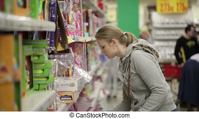 Young woman is choosing toys for her kid.