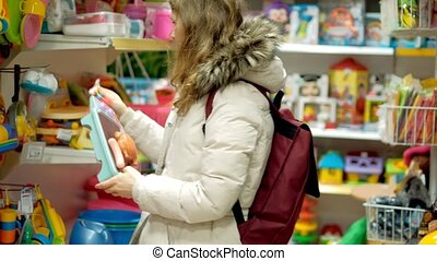 Young woman is choosing toys present for her kid. Middle shot with shoppers in background.