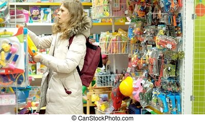 Young woman is choosing toys present for her kid. Middle...