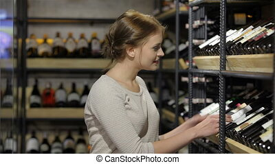Young woman is choosing wine in the supermarket