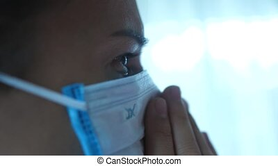 Young woman is coughing, feeling unwell, sick with wearing a medical mask. Close up