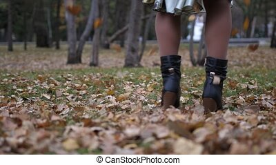 young woman is danced on a background of autumn leaf fall, walking in the park