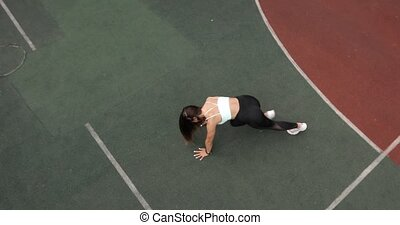 Young woman is doing plank exersice flexing legs in dynamic on sport ground.