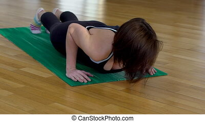 Young woman is doing press up on floor in sports club....