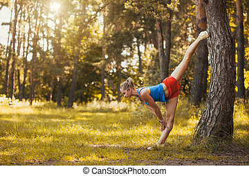 young woman is doing warming up before running in the forest on a beautiful summer day