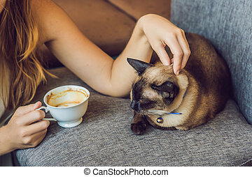 Young woman is drinking coffee and stroking the cat