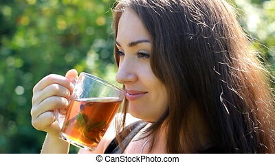 Young woman is drinking tea with mint in nature.