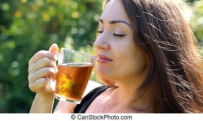 Young woman is drinking tea with mint outdoor.