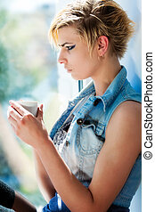 Young woman is drinking tea