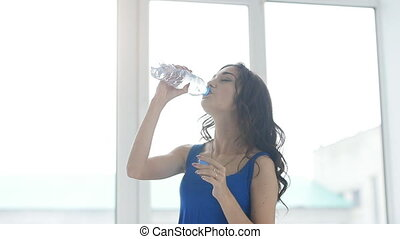 Young woman is drinking water after training on the white interior
