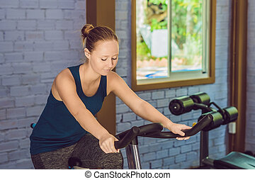 Young woman is engaged on a bicycle in the gym