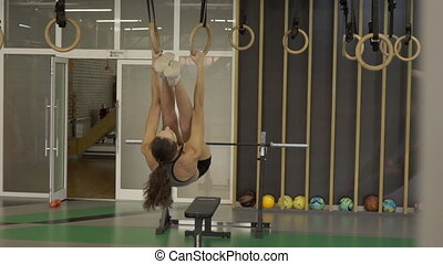 Young woman is exercising with loops in sports club. Fitness...