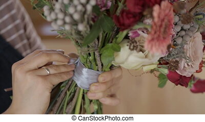 Young woman is fixing satin ribbon on floral bouquet...