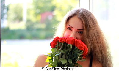 Young woman is given a bouquet of red roses. Birthday. Celebration. Gift