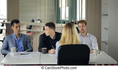 Young woman is having work interview in front of men.