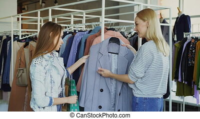 Young woman is helping her friend to find coat. She is...