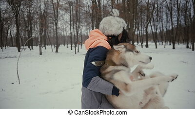 Young woman is holding a hussel dog in her arms in a snowy winter park. Beautiful girl playing with a dog