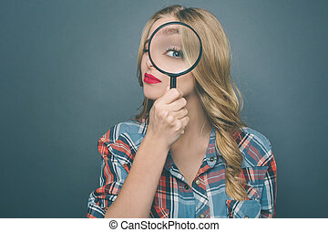 Young woman is holding a magnifying glass and looking straight through it. She is very serious. Isolated on blue background.