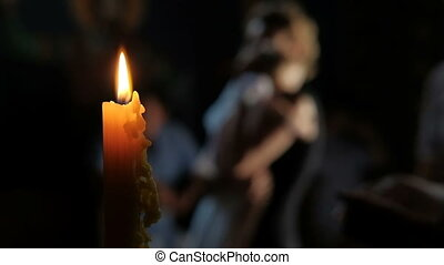Young woman is holding small child standing near burning candle in dark night.