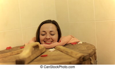 Young woman is in cedar barrel in spa salon indoors....