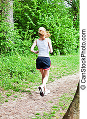young woman is jogging in forest