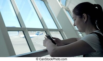 Young woman is looking at mobile phone screen waiting her flight in airport.