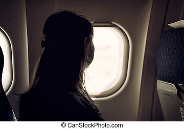 Young woman is looking through a window in the aircraft.
