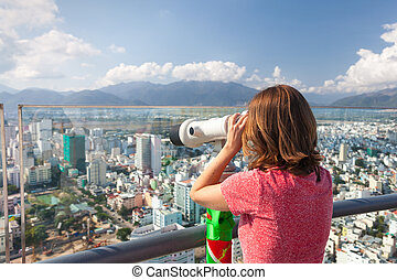 Young woman is looking through the tower viewer