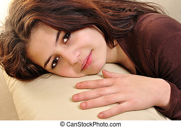 young woman is lying on a couch