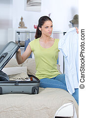 young woman is packing a suitcase